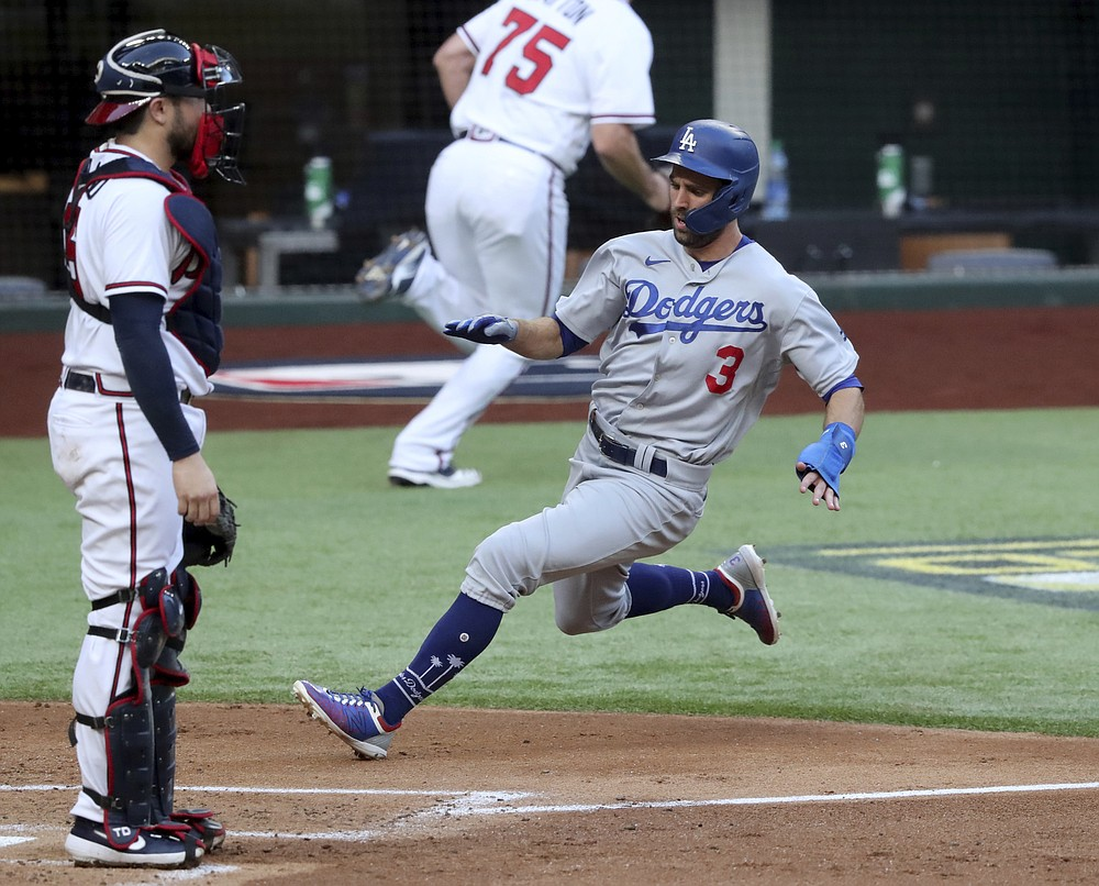 Los Angeles Dodgers' Chris Taylor, center, scores past Atlanta Braves catcher Travis d'Arnaud during the first inning in Game 3 of a baseball National League Championship Series Wednesday, Oct. 14, 2020, in Arlington, Texas.  (Curtis Compton/Atlanta Journal-Constitution via AP)