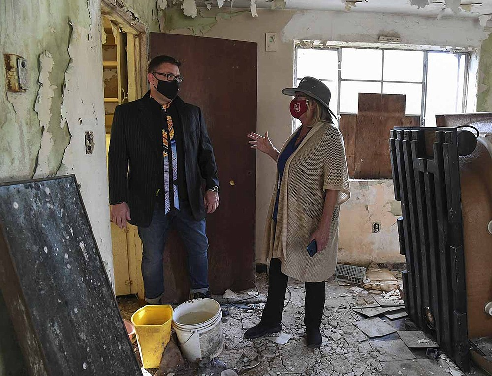 Realtor Chris Rix, left, and Diana Hampo talk during a tour of Perry Plaza on Oct. 8. Rix recently purchased the property for a restoration project. - Photo by Grace Brown of The Sentinel-Record