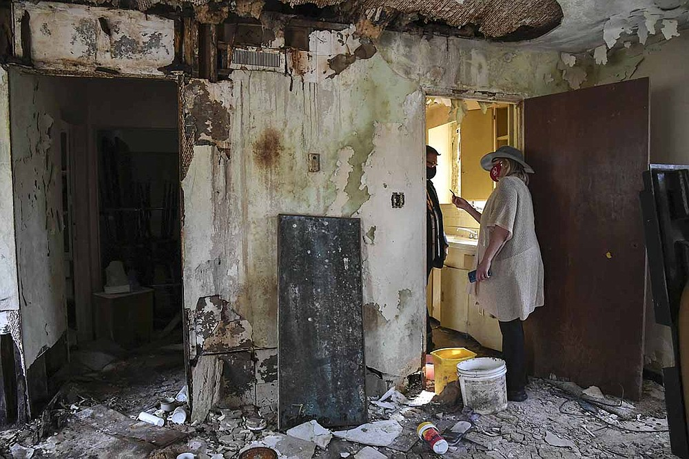 Realtor Chris Rix, left, and Diana Hampo explore one of the rooms at Perry Plaza on Oct. 8. - Photo by Grace Brown of The Sentinel-Record