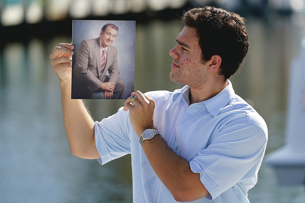 Freddy Vallejo Jr. holds a photograph of his grandfather Jorge Vallejo, Saturday, Sept. 26, 2020, at the family vacation home in Key Largo, in the Florida Keys. Jorge Vallejo, a retired OB-GYN, and his son Carlos Vallejo, who practiced internal medicine, died of the coronavirus within weeks of one another in South Florida. (AP Photo/Lynne Sladky)