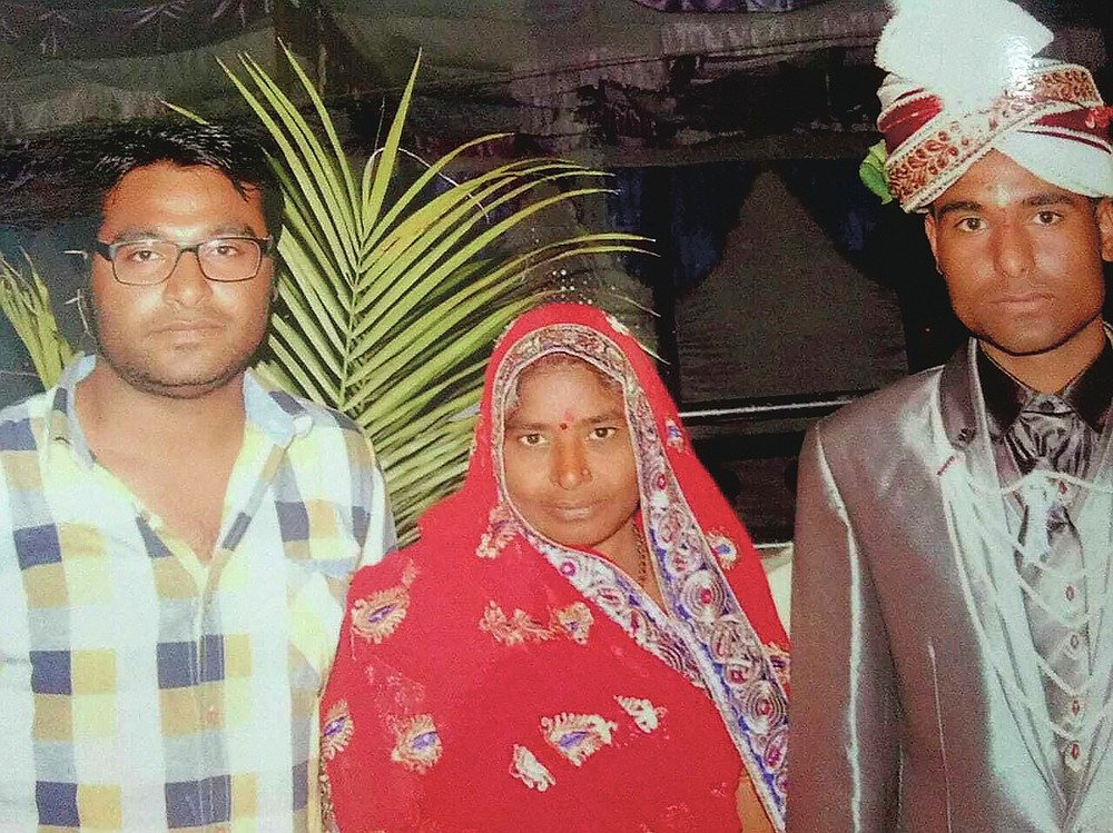 In this Feb. 3, 2014, photo, Joginder Chaudhary, left, and Kapil pose for a picture with their mother Premlata on Kapil's wedding day, in Jhantala, Madhya Pradesh, India. After the virus killed the 27-year-old Chaudhary in late July 2020, his mother wept inconsolably. With her son gone, Premlata Chaudhary said, how could she go on living? Three weeks later, on Aug. 18, the virus took her life, too — yet another number in an unrelenting march toward a woeful milestone. (Courtesy of Kapil Chaudhary via AP)