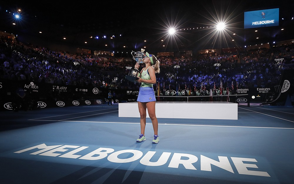FILE - In this Feb. 1, 2020, file photo, Sofia Kenin, of the United States, kisses her trophy after defeating Spain's Garbine Muguruza in the women's singles final at the Australian Open tennis championship in Melbourne, Australia. Australian Open chief executive Craig Tiley says he wants international tennis players arriving for January's first Grand Slam of 2021 to be exempt from a current 14-day hotel quarantines. (AP Photo/Lee Jin-man, File)