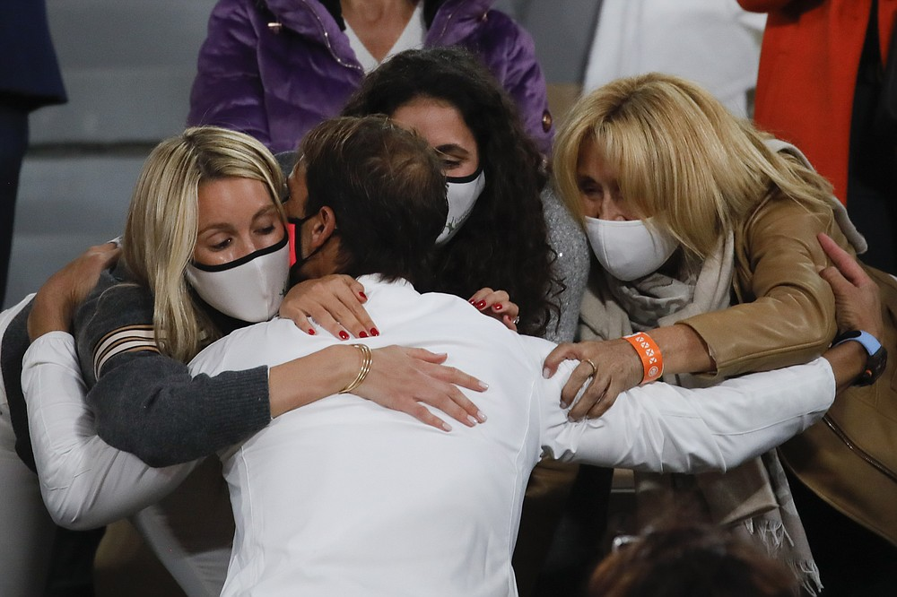 Spain's Rafael Nadal kisses his wife, left, and family members as he celebrates winning the final match of the French Open tennis tournament against Serbia's Novak Djokovic in three sets, 6-0, 6-2, 7-5, at the Roland Garros stadium in Paris, France, Sunday, Oct. 11, 2020. (AP Photo/Christophe Ena)