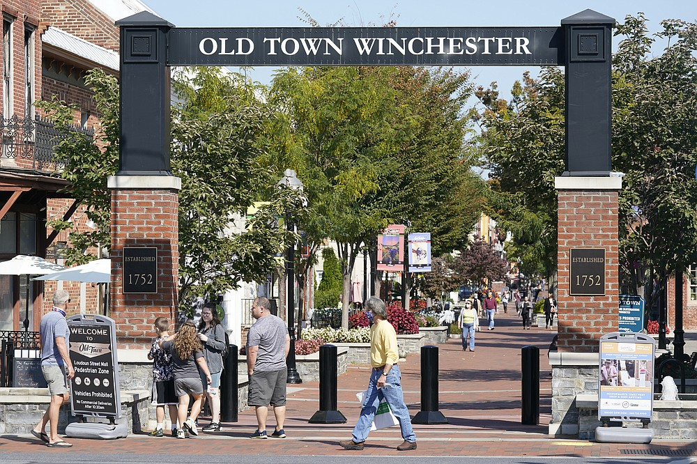 Pedestrians walk along the downtown mall area in the Old Town Wednesday Oct. 7, 2020, in Winchester, Va.  The viral pandemic has hammered small businesses across the United States, an alarming trend for an economy that's trying to rebound from the deepest, fastest recession in U.S. history.  Small companies are struggling in Winchester, a city of 28,000 that works hard to promote and preserve local enterprises.  (AP Photo/Steve Helber)