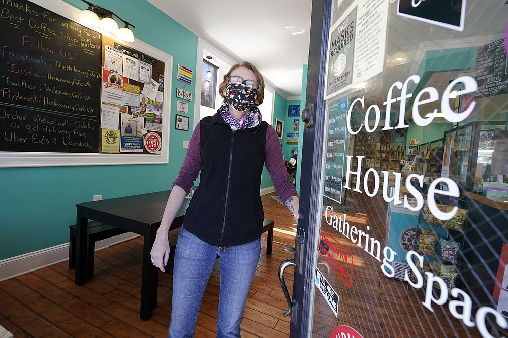 Victoria Leigh Kidd,  owner of Hideaway Café, opens the front door of her shop in the Old Town area Wednesday Oct. 7, 2020, in Winchester, Va.  The viral pandemic has hammered small businesses across the United States, an alarming trend for an economy that's trying to rebound from the deepest, fastest recession in U.S. history.  Small companies are struggling in Winchester,  a city of 28,000 that works hard to promote and preserve local enterprises. (AP Photo/Steve Helber)