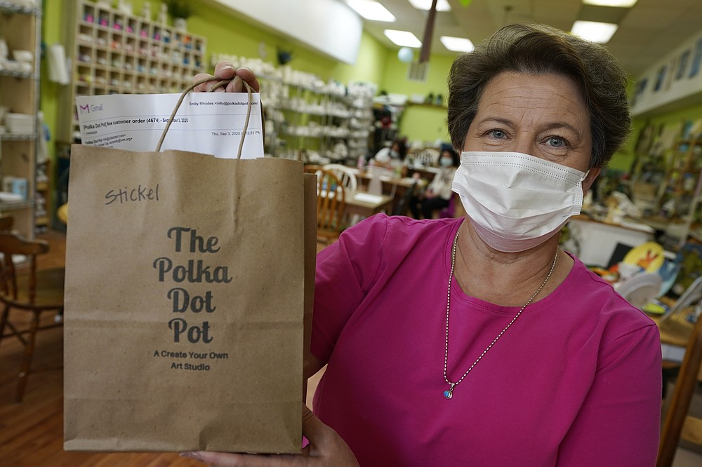 Polka Dot Pot owner Emily Rhodes holds a take home bag at her shop in the Old Town area Wednesday Oct. 7, 2020, in Winchester, Va.  The viral pandemic has hammered small businesses across the United States, an alarming trend for an economy that's trying to rebound from the deepest, fastest recession in U.S. history.  Small companies are struggling in Winchester, a city of 28,000 that works hard to promote and preserve local enterprises.  (AP Photo/Steve Helber)