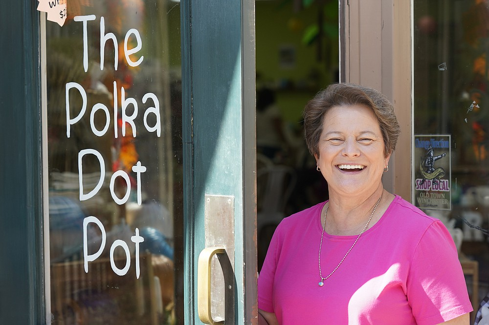 Polka Dot Pot owner Emily Rhodes poses at the front door of her shop In the Old Town area Wednesday Oct. 7, 2020, in Winchester, Va.   The viral pandemic has hammered small businesses across the United States, an alarming trend for an economy that's trying to rebound from the deepest, fastest recession in U.S. history.  Small companies are struggling in Winchester,  a city of 28,000 that works hard to promote and preserve local enterprises.  (AP Photo/Steve Helber)