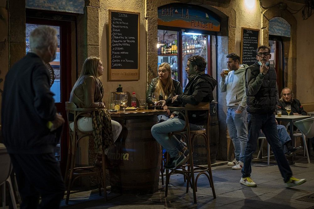 Customers sit outside a bar in Barcelona, Spain, Thursday Oct. 15, 2020. Authorities in northeastern Spain ordered shut all bars and restaurants for two weeks as part of fresh restrictions against the spread of the new coronavirus. (AP Photo/Emilio Morenatti)