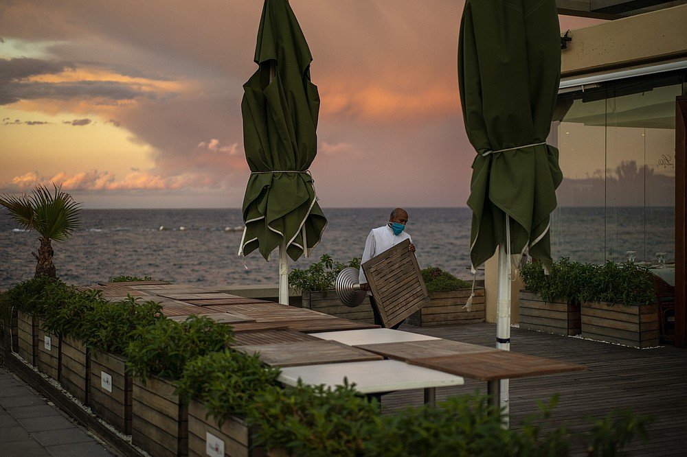 A waiter removes tables outside a restaurant in Barcelona, Spain, Thursday Oct. 15, 2020. Authorities in northeastern Spain ordered shut all bars and restaurants for two weeks as part of fresh restrictions against the spread of the new coronavirus. (AP Photo/Emilio Morenatti)