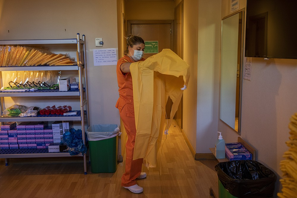 Nurse Paula Gonzalez dresses in full protective gear before entering the red zone of a hotel for COVID-19 patients under quarantine in Leganes, outskirts of Madrid, Spain, Thursday, Oct. 15, 2020. The red zone marks the hotel area where coronavirus patients stay. (AP Photo/Bernat Armangue)