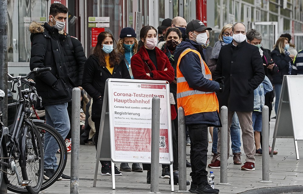 People wait in line for a COVID-19 test at a coronavirus test center in Cologne, Germany, Thursday, Oct. 15, 2020. The city exceeded the important warning level of 50 new infections per 100,000 inhabitants in seven days. More and more German cities become official high risk corona hotspots with travel restrictions within Germany. (AP Photo/Martin Meissner)