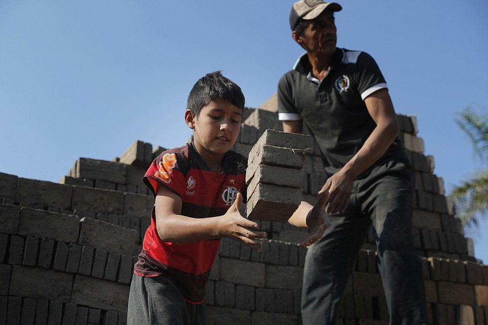Alejandro, 9, catches bricks to pass over to a man who puts them in the kiln at a brick factory run by his uncles in Tobati, Paraguay, Monday, Aug. 31, 2020. Members of brickmaking families said school closures due to COVID-19, scheduled to last at least until December, have led to many children and adolescents working longer hours, making it difficult to complete their virtual schoolwork. (AP Photo/Jorge Saenz)