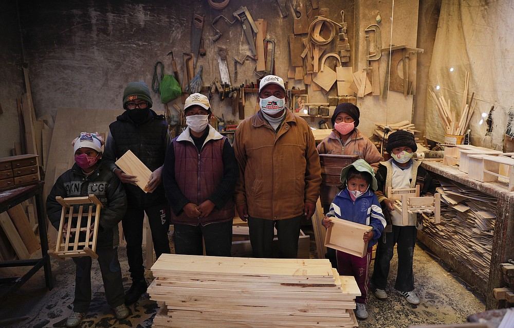 Wearing masks to curb the spread of the new coronavirus, the Delgado family poses for a photo in their carpentry workshop in El Alto, Bolivia, Friday, Aug. 28, 2020. After the government canceled the school year, the five children between ages 6 and 14 work in the carpentry workshop with their parents. (AP Photo/Juan Karita)
