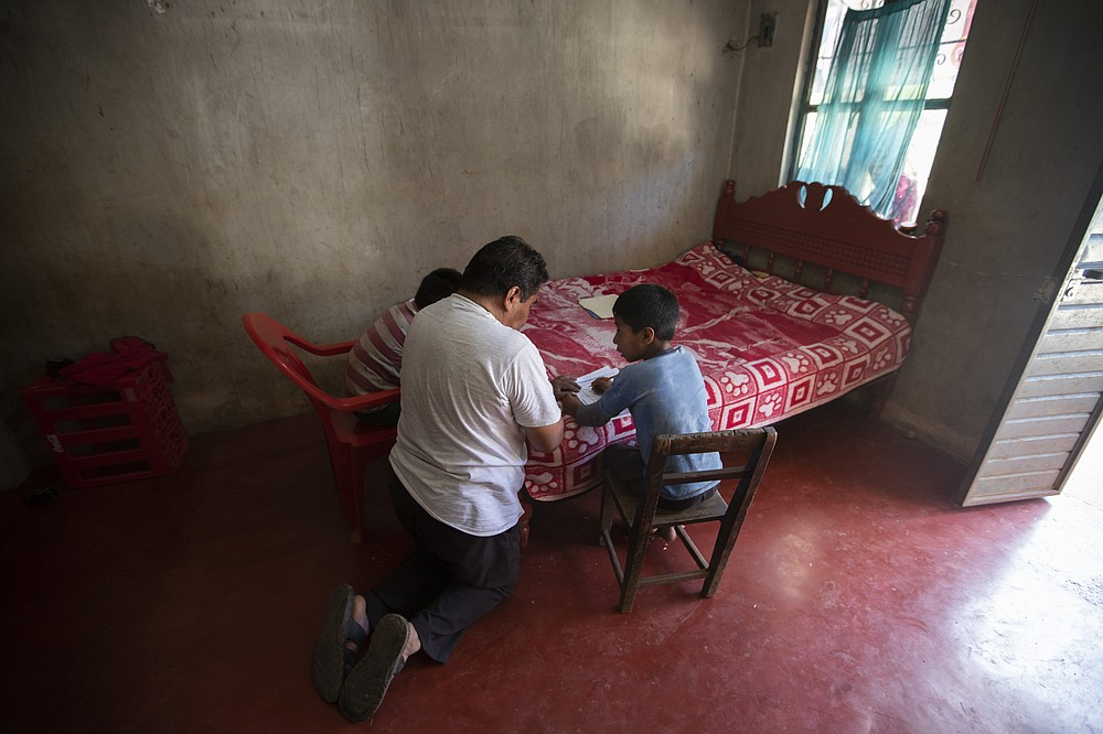 "Using a bed as a desk, Agustin Vazquez helps his sons Samuel and Hector with their schoolwork handed out by teachers amid the new coronavirus pandemic at their home in Nuevo Yibeljoj, Chiapas state, Mexico, Friday, Sept. 11, 2020. ""I try, but it's not the same as a teacher, because I'm a farmer,"" said Agustín.  (AP Photo/Eduardo Verdugo)"