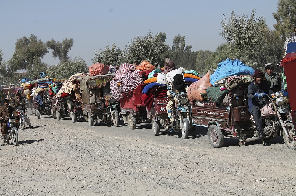 Afghan families leave their houses after fighting between the Afghan military and Taliban insurgents in Helmand province, southern of Afghanistan, Tuesday, Oct. 13, 2020. (AP Photo/Abdul Khaliq)