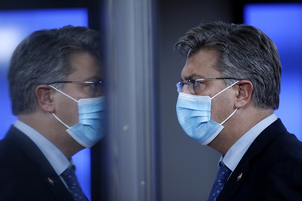 Croatia's Prime Minister Andrej Plenkovic is reflected in a glass door as he leaves during departures at an EU summit in Brussels, Thursday, Oct. 15, 2020. European Union leaders met in person for the first day of a two-day summit, amid the worsening coronavirus pandemic, to discuss topics ranging from Brexit to climate and relations with Africa. (AP Photo/ Francisco Seco, Pool)
