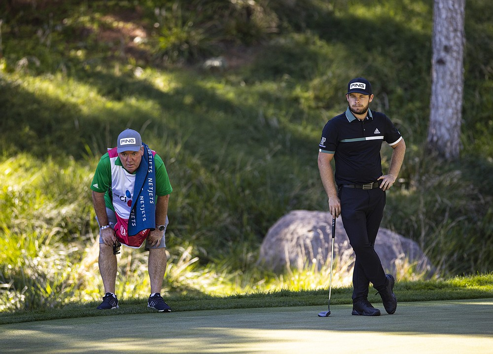 Tyrrell Hatton, right, keeps an eye on the ninth green with his caddie, Mick Donaghy, during the second round of the CJ Cup golf tournament at the Shadow Creek Golf Course, Friday, Oct. 16, 2020, in North Las Vegas. (Chase Stevens/Las Vegas Review-Journal via AP)