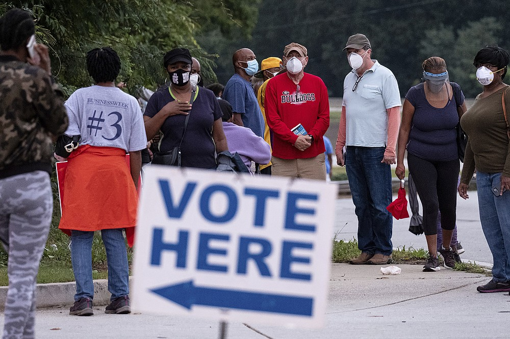 People wait in line to vote in Decatur, Ga., Monday, Oct. 12, 2020. (Ben Gray/Atlanta Journal-Constitution via AP)
