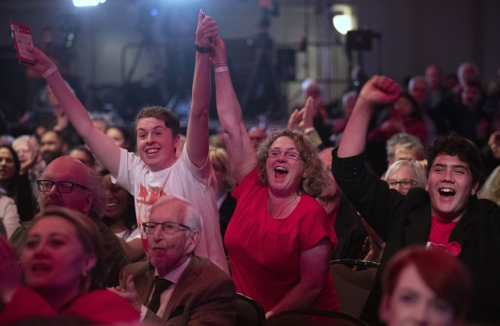 New Zealand Labour Party supporters react as results are showed on a screen at a party event after the polls closed in Auckland, New Zealand, Saturday, Oct. 17, 2020. (AP Photo/Mark Baker)