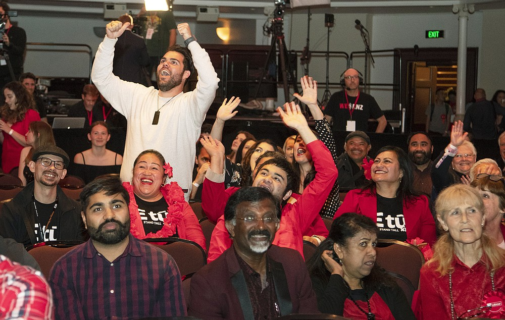 New Zealand Labour Party supporters react as results are showed on a screen at a party event after the polls closed in Auckland, New Zealand, Saturday, Oct. 17, 2020. Polling places closed and vote counting began on election day in New Zealand on Saturday as Prime Minister Jacinda Ardern seeks a second term. (AP Photo/Mark Baker)