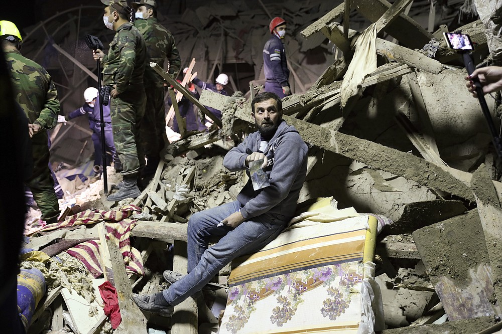 A man shows a photo to a journalist, sitting in his house as soldiers and firefighters search for survivors in a residential area that was hit by rocket fire overnight by Armenian forces, early Saturday, Oct. 17, 2020, in Ganja, Azerbaijan's second largest city, near the border with Armenia. Azerbaijan has accused Armenia of striking its second-largest city with a ballistic missile that killed at least 13 civilians and wounded 50 others in a new escalation of their conflict over Nagorno-Karabakh. (AP Photo/Aziz Karimov)