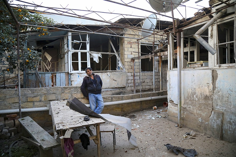 A man stands in a yard of his destroyed house in a residential area that was hit by rocket fire overnight by Armenian forces, early Saturday, Oct. 17, 2020, in Gyanga, Azerbaijan's second largest city, near the border with Armenia. (AP Photo/Aziz Karimov)