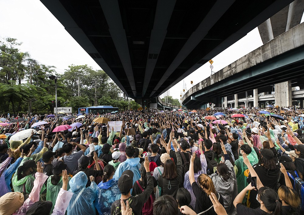 Pro-democracy protesters raise three-finger salutes, a symbol of resistance, as they gather during a protest near a main train station in Bangkok, Thailand, Saturday, Oct. 17, 2020. The authorities in Bangkok shut down mass transit systems and set up roadblocks Saturday as Thailand's capital braced for a fourth straight day of determined anti-government protests. (AP Photo/Sakchai Lalit)