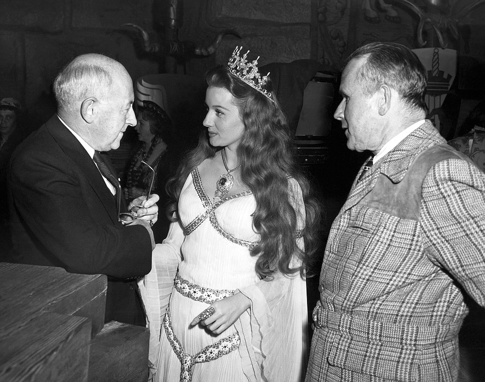 FILE - In this Dec. 16, 1947 file photo, Producer- director Cecil B. DeMille, left, gives actress Rhonda Fleming some advice as Tay Garnett, right, listens in Hollywood, Calif.  Actress Rhonda Fleming, the fiery redhead who appeared with Burt Lancaster, Kirk Douglas, Charlton Heston, Ronald Reagan and other film stars of the 1940s and 1950s, has died, Wednesday, Oct. 14, 2020. She was 97. (AP Photo/File)