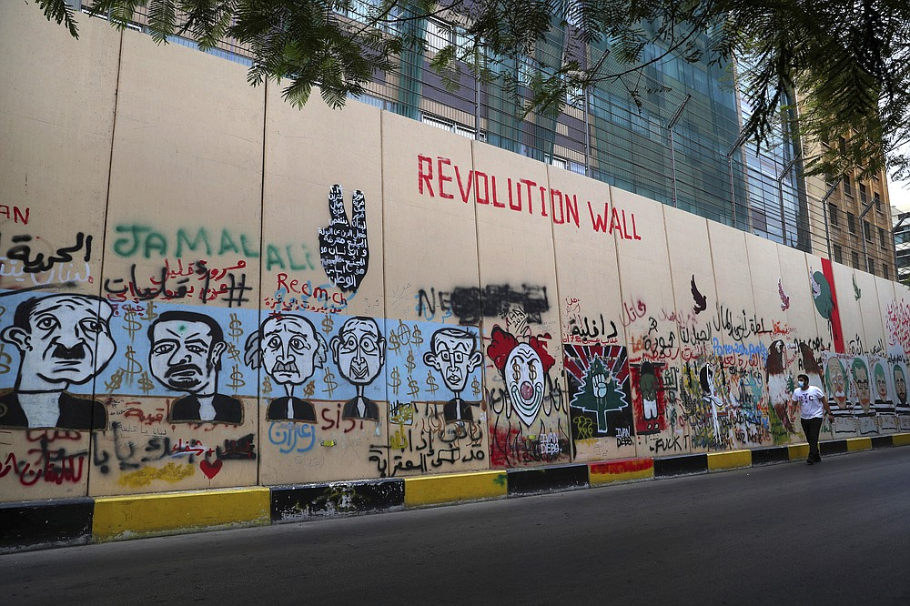 A man walks past the wall of United Nations Headquarters, decorated with graffitis painting in Beirut, Lebanon, Monday, Oct. 12, 2020. A year ago, hundreds of thousands of Lebanese took to the streets in protests nationwide that raised hopes among many for a change in a political elite that over that decades has run the country into the ground.  (AP Photo/Bilal Hussein)