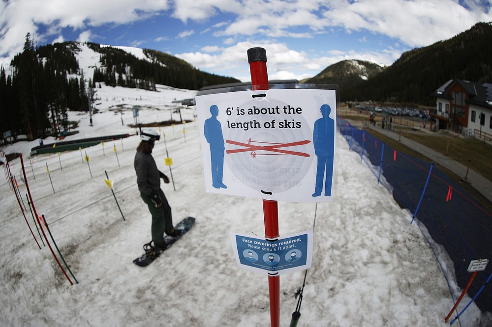 FILE - In this Wednesday, May 27, 2020, file photo, a sign reminds skiers and snowboarders to practice social distancing while wearing a face covering in lift lines at the reopening of Arapahoe Basin Ski Resort, which closed in mid-March to help in the effort to stop the spread of the new coronavirus, in Keystone, Colo. The virus will create a new environment for skiers and snowboarders in the winter sports season ahead. (AP Photo/David Zalubowski, File)