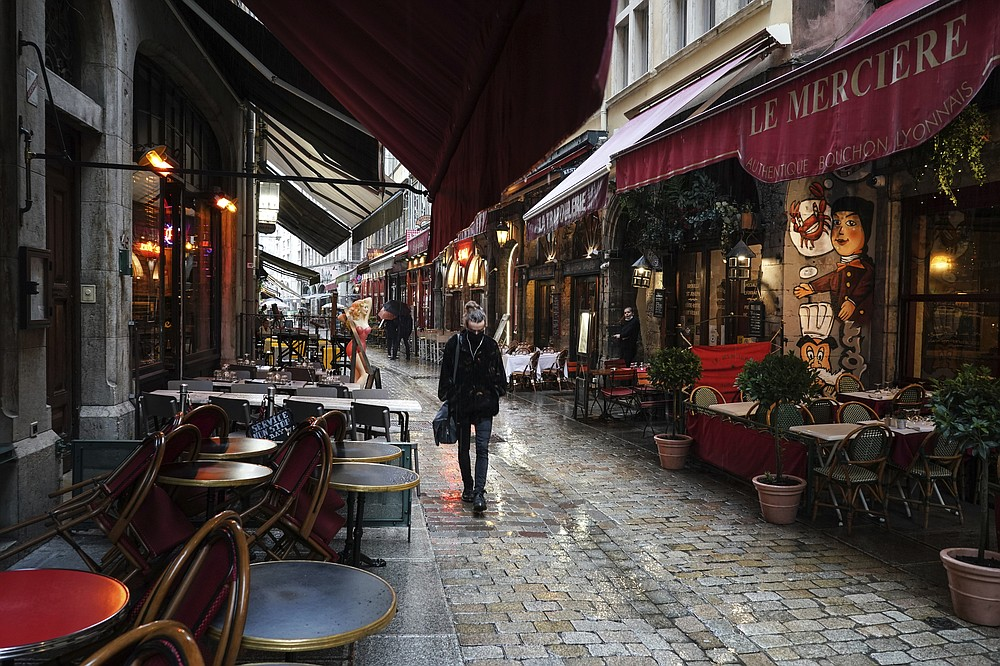 FILE - In this  Friday, Oct. 2, 2020 file photo, a woman walks by empty restaurants in the center of Lyon, central France. Europe's economy was just catching its breath from what had been the sharpest recession in modern history. A resurgence in coronavirus cases this month, Oct. 2020, risks undoing that and will likely turn what was meant to be a period of healing for the economy into a lean winter of job losses and bankruptcies. (AP Photo/Laurent Cipriani, File)