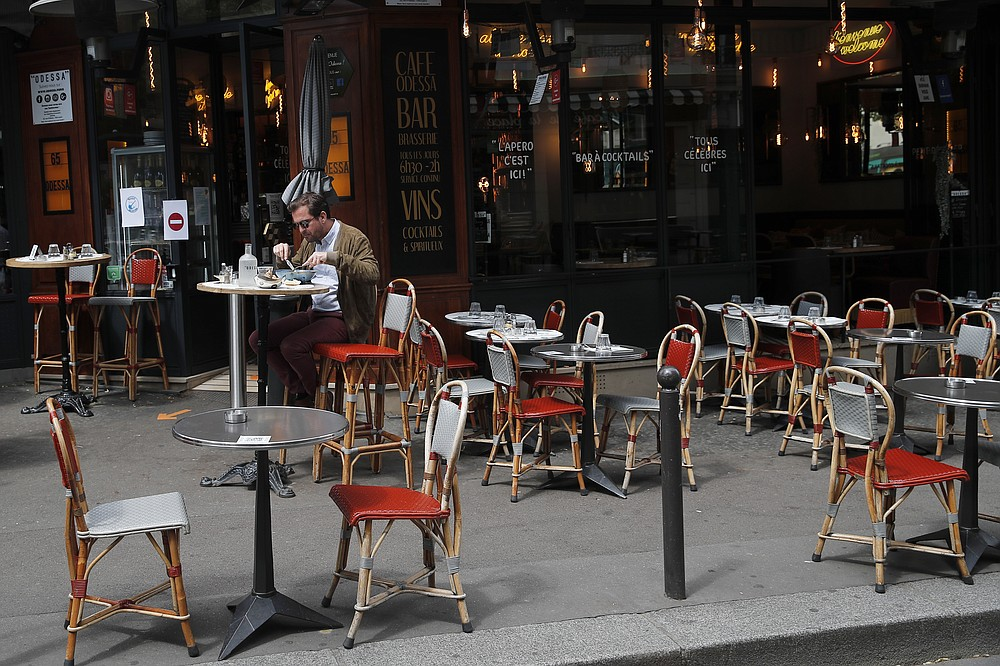 FILE - In this Monday, June 15, 2020 file photo, a man takes his lunch on a terrace at a restaurant, in Paris. Europe's economy was just catching its breath from what had been the sharpest recession in modern history. A resurgence in coronavirus cases this month, Oct. 2020, risks undoing that and will likely turn what was meant to be a period of healing for the economy into a lean winter of job losses and bankruptcies. (AP Photo/Francois Mori, File)