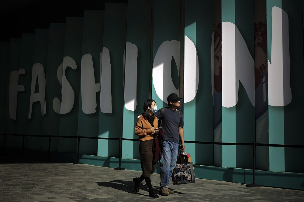 A couple with their purchased goods walk through the capital city's popular shopping mall in Beijing, Monday, Oct. 19, 2020. China's shaky economic recovery from the coronavirus pandemic is gaining strength as consumers return to shopping malls and auto dealerships while the United States and Europe endure painful contractions.(AP Photo/Andy Wong)