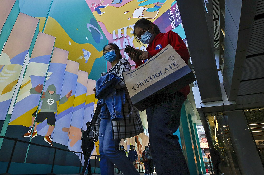 Shoppers wearing face masks to help curb the spread of the coronavirus with their purchased goods walk through the capital city's popular shopping mall in Beijing, Monday, Oct. 19, 2020. China's shaky economic recovery from the coronavirus pandemic is gaining strength as consumers return to shopping malls and auto dealerships while the United States and Europe endure painful contractions. (AP Photo/Andy Wong)