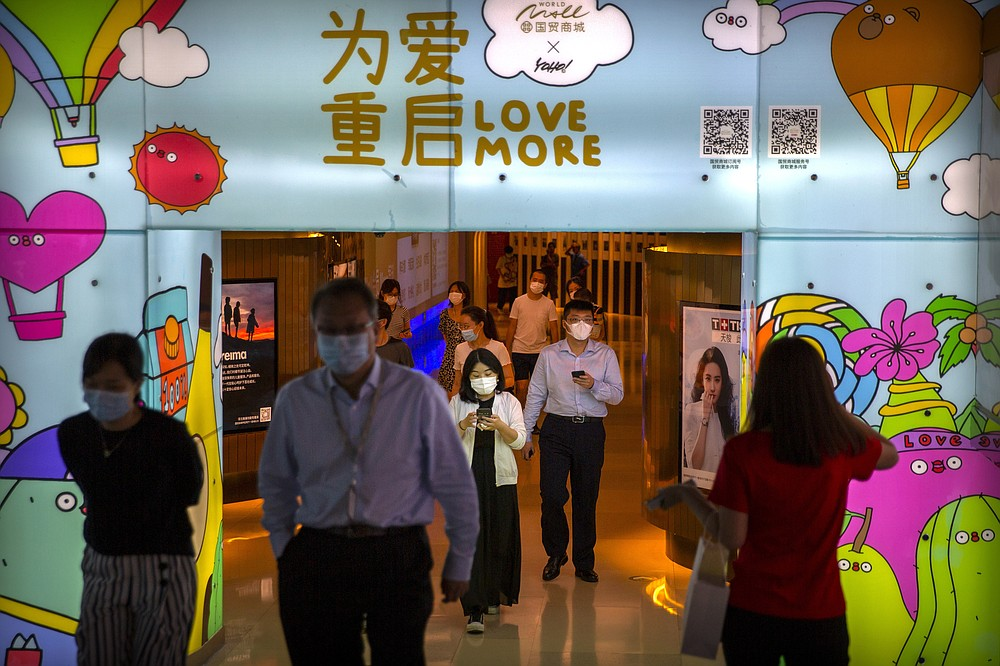 FILE - In this Aug. 14, 2020, file photo, people wearing face masks to protect against the coronavirus walk through a shopping mall in Beijing. China's economic growth accelerated to 4.9% over a year earlier in the latest quarter as a shaky recovery from the coronavirus pandemic gathered strength. (AP Photo/Mark Schiefelbein, File)