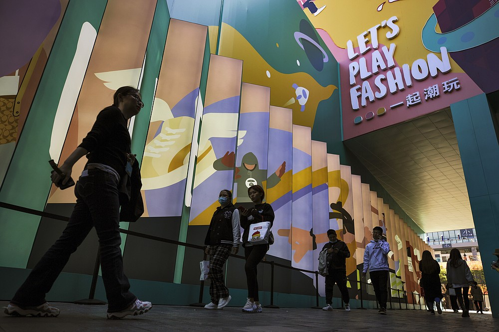Shoppers wearing face masks to help curb the spread of the coronavirus walks through the capital city's popular shopping mall in Beijing, Monday, Oct. 19, 2020. China's shaky economic recovery from the coronavirus pandemic is gaining strength as consumers return to shopping malls and auto dealerships while the United States and Europe endure painful contractions. (AP Photo/Andy Wong)