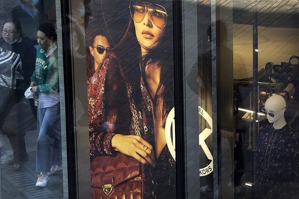 Shoppers, some wearing a face mask to help curb the spread of the coronavirus are reflected on a fashion boutique's window panel as they walk through the capital city's popular shopping mall in Beijing, Monday, Oct. 19, 2020. China's shaky economic recovery from the coronavirus pandemic is gaining strength as consumers return to shopping malls and auto dealerships while the United States and Europe endure painful contractions. (AP Photo/Andy Wong)