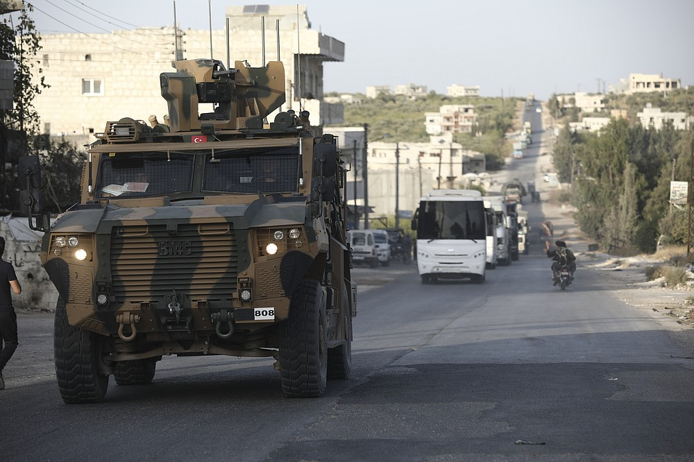 Turkish military convoy drives through the village of Urum al-Jawz, in Idlib province, Syria, Tuesday, Oct. 20, 2020. Turkish troops in northwestern Syria have been evacuating one of their largest military bases in the area, which was surrounded by Syrian government troops for months, activists said Tuesday. There was no immediate comment from Turkish officials. (AP Photo/Ghaith Alsayed)
