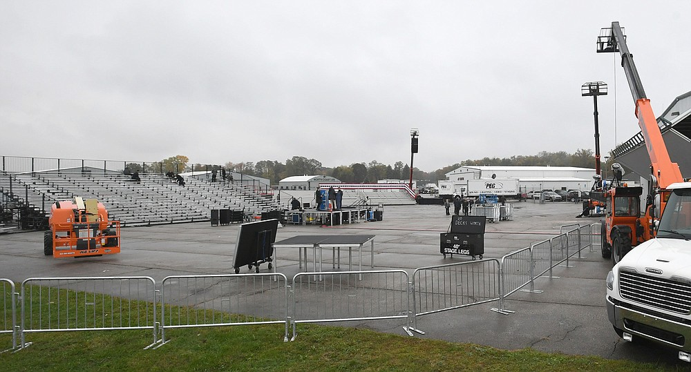 In advance of a rally for President Donald Trump, the stage and seating are shown, Monday, Oct. 19, 2020, being set up near a North Coast Air plane hangar, at right,  on the tarmac near the northwest corner of the Erie International Airport in Millcreek Township, Erie County, Pa.Trump's rally is scheduled for Tuesday evening, Oct. 20. (Christopher Millette/Erie Times-News via AP)