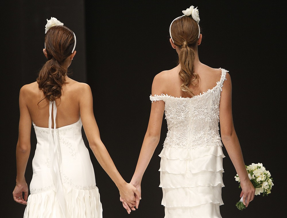 """FILE -- In this Thursday, Oct. 23, 2014 file photo, models hold hands on the catwalk during a wedding fashion show with same-sex couples, dubbed """"The rainbow wedding fashion show"""", part of a 'wedding fair' taking place in Rome. Pope Francis endorsed same-sex civil unions for the first time as pope while being interviewed for the feature-length documentary """"Francesco,"""" which premiered Wednesday, Oct. 21 2020 at the Rome Film Festival.  (AP Photo/Domenico Stinellis)"""