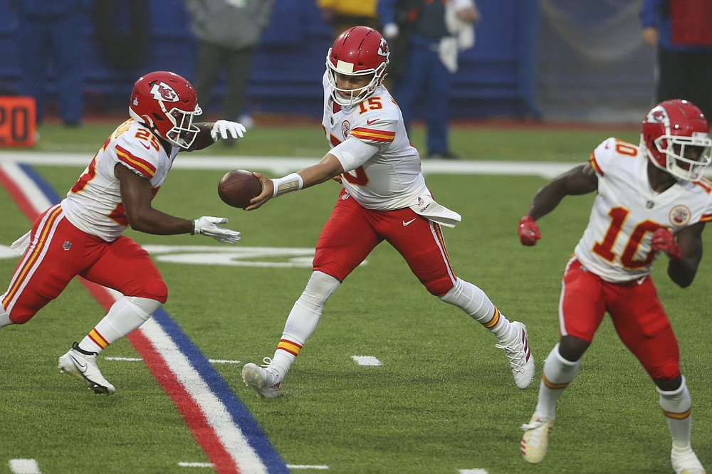 Kansas City Chiefs quarterback Patrick Mahomes, center, hands off the ball to Clyde Edwards-Helaire, left, during the first half of an NFL football game against the Buffalo Bills, Monday, Oct. 19, 2020, in Orchard Park, N.Y. (AP Photo/Jeffrey T. Barnes)