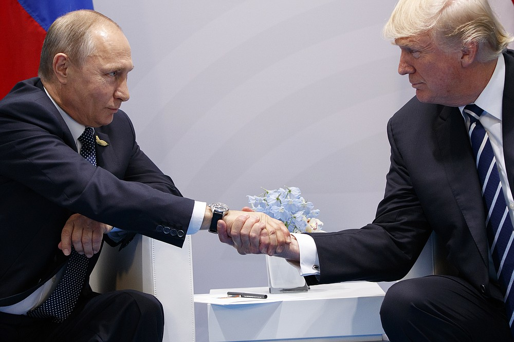 FILE - In this July 7, 2017, file photo, President Donald Trump shakes hands with Russian President Vladimir Putin at the G20 Summit in Hamburg. Trump has strenuously sought to keep an entente cordiale, an informal alliance of sorts, with Putin. This in the face of his own intelligence agencies' confirmation of Moscow's interference in the 2016 election, which sought to aid him, and Moscow secretly offering bounties to the Taliban for the deaths of Americans in Afghanistan.   (AP Photo/Evan Vucci, File)