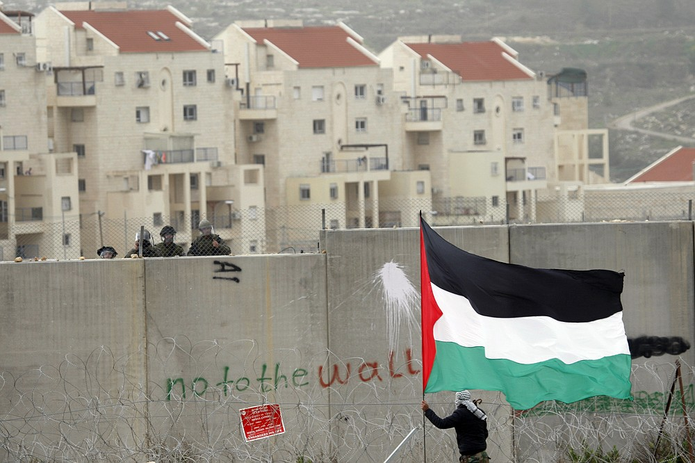 FILE- In this Friday, Feb. 17, 2012 file photo, the West Bank Jewish settlement of Modiin Illit rises in the background while a protestor waves a Palestinian flag in front of Israeli troops during a protest against Israel's separation barrier in the West Bank village of Bilin. Trump's self-proclaimed ''deal of the century' was anything but for the Palestinians' when it was released earlier this year, effectively greenlighting Israeli annexation in the occupied West Bank, killing off the two-state solution in an already moribund peace process and upending decades of official U.S. policy with regards settlements.(AP Photo/Majdi Mohammed, File)