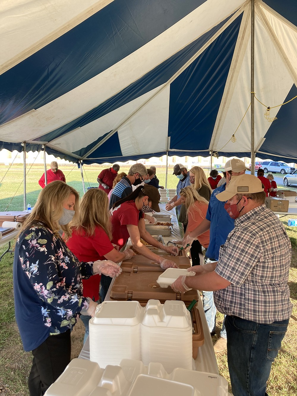 Volunteers prepare trays of fish and chicken at the 68th annual Pine Bluff Chamber of Commerce fish fry on Thursday. (Pine Bluff Commercial/Byron Tate)