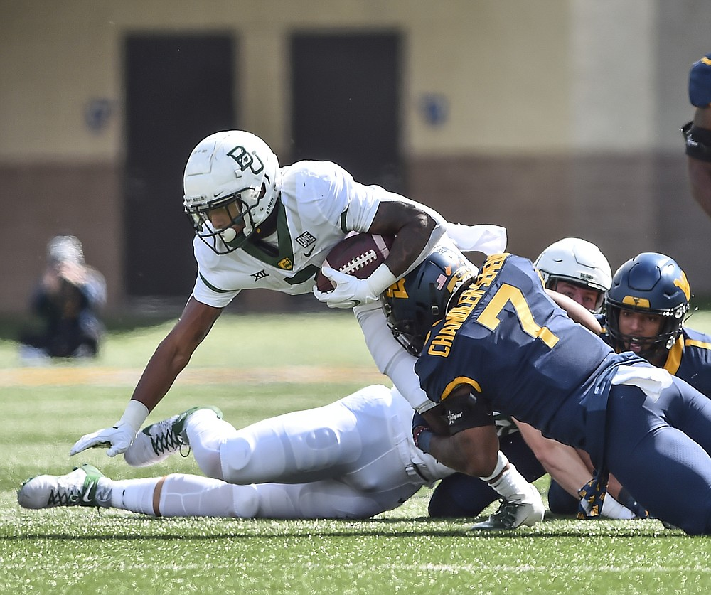 Baylor running back John Lovett (7) is tackled by West Virginia linebacker Josh Chandler-Semedo (7) during an NCAA college football game, Saturday, Oct. 3, 2020, in Morgantown, W.Va. (William Wotring/The Dominion-Post via AP)