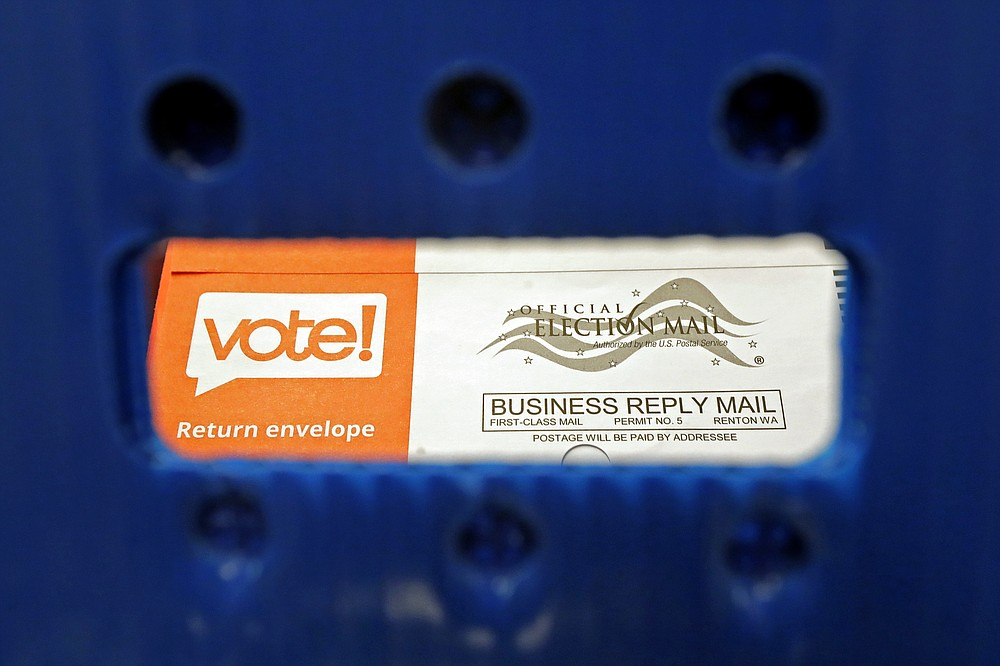 FILE - In this Aug. 5, 2020, file photo a vote-by-mail ballot is shown as viewed through the handle of a sorting tray at the King County Elections headquarters in Renton, Wash., south of Seattle. U.S. Postal Service records show delivery delays have persisted across the country as millions of Americans began voting by mail, raising the possibility of ballots being rejected because they arrive too late. Postal data covering the beginning of October show nearly all of the agency's delivery regions missing agency targets of having more than having more than 95% of first-class mail arrive within five days. (AP Photo/Ted S. Warren, File)