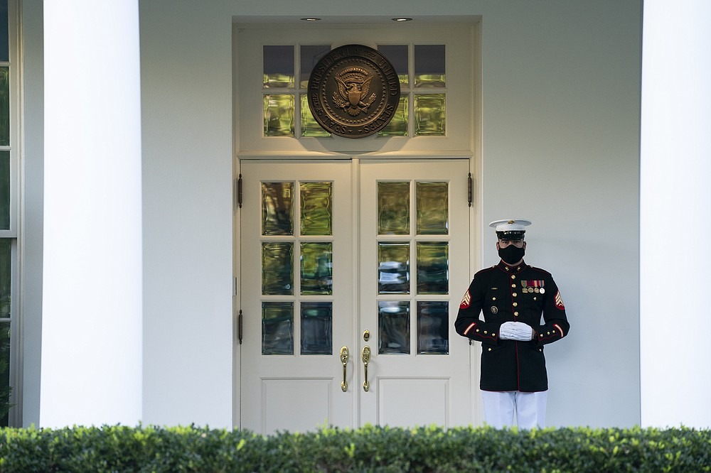 In this Oct. 8, 2020 photo, a Marine is posted outside the West Wing of the White House, signifying the President is in the Oval Office, in Washington.  Courts nationwide have seen a flurry of litigation over the 2020 presidential election as both major parties jockey for every advantage. President Donald Trump and Democrat Joe Biden's campaigns are assembling armies of powerful lawyers. (AP Photo/Evan Vucci)