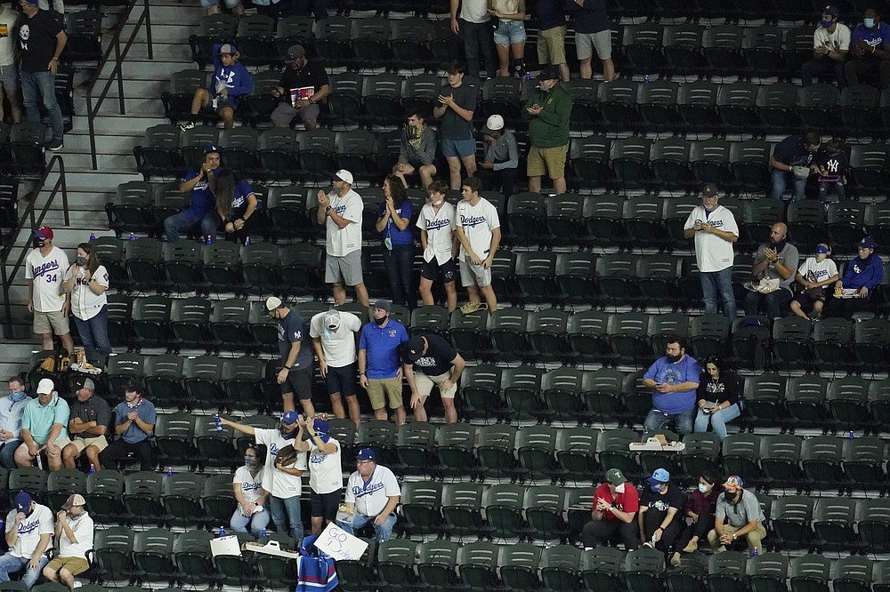 Fans watch during the fourth inning in Game 2 of the baseball World Series between the Los Angeles Dodgers and the Tampa Bay Rays Wednesday, Oct. 21, 2020, in Arlington, Texas. (AP Photo/David J. Phillip)