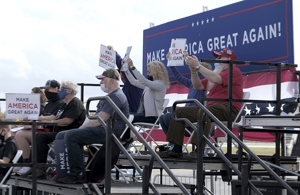 Supporters of Vice President Mike Pence hold up signs during his rally at the Grand Aire hanger of the Eugene F. Kranz Toledo Express Airport in Swanton, Ohio on Friday, Oct. 23, 2020.  (Lori King/The Blade via AP)