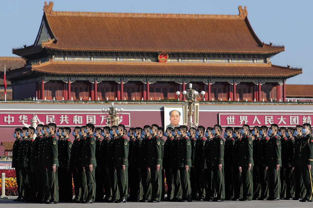 Chinese paramilitary policemen wearing face masks to help curb the spread of the coronavirus stand in formation on Tiananmen Square before the commemorating conference on the 70th anniversary of China's entry into the 1950-53 Korean War, at the Great Hall of the People in Beijing Friday, Oct. 23, 2020. (AP Photo/Andy Wong)